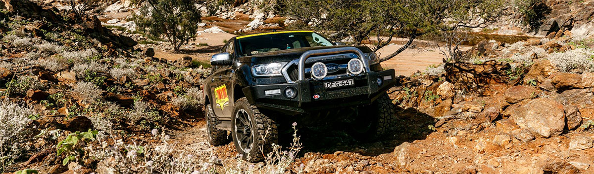 A Ford Ranger with lift kit drives through rocky terrain.